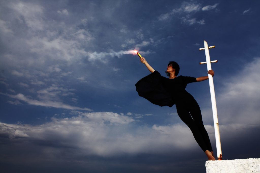 Image of lady dressed in black holding herself by a white pole